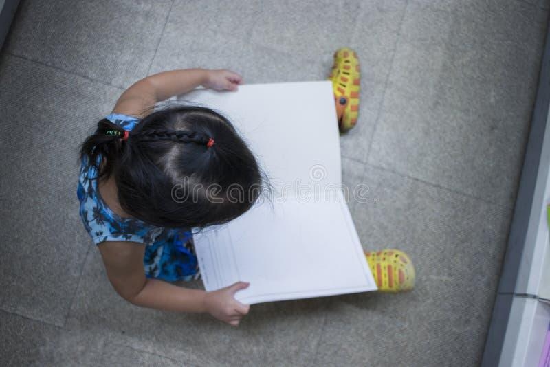 Weinig Kind onderzoekt en lezing een boek in boekhandel hoogste mening stock foto
