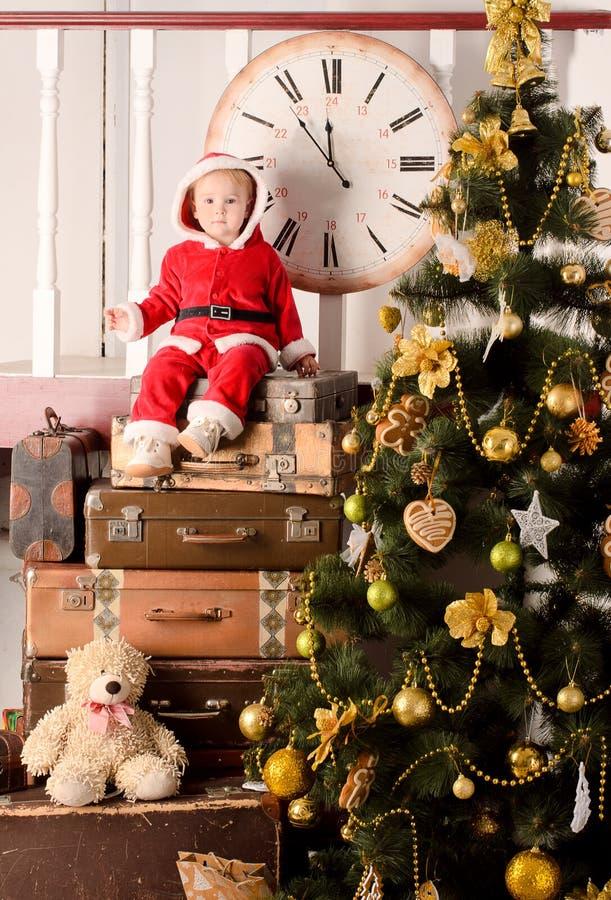 Weinig kind in santakostuum bij Kerstmisboom royalty-vrije stock afbeeldingen