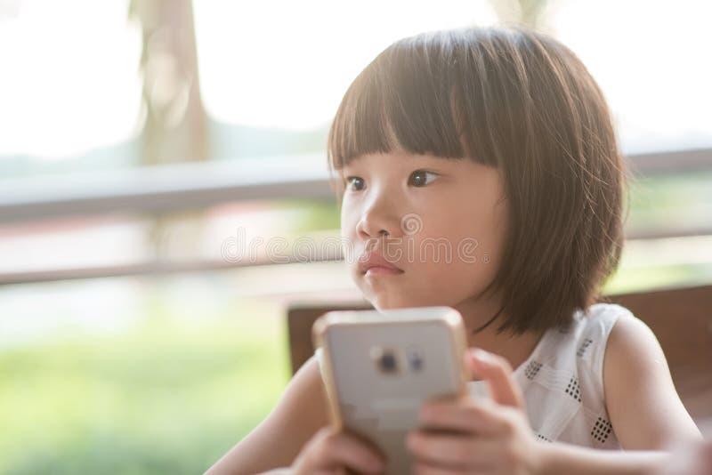 Weinig kind wijdde zich aan slimme telefoon stock afbeeldingen