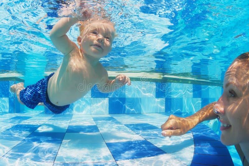 Weinig kind zwemmen onderwater in pool met moeder stock foto
