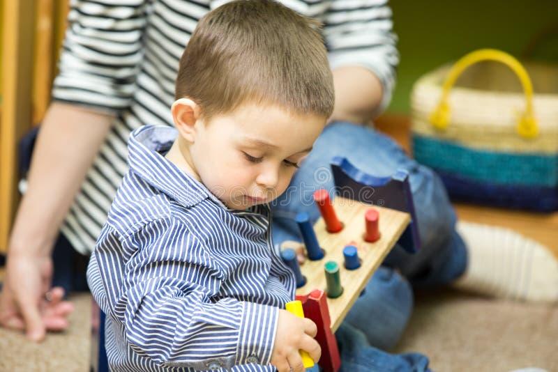 Weinig kindjongen die in kleuterschool in Montessori-Klasse spelen stock afbeeldingen