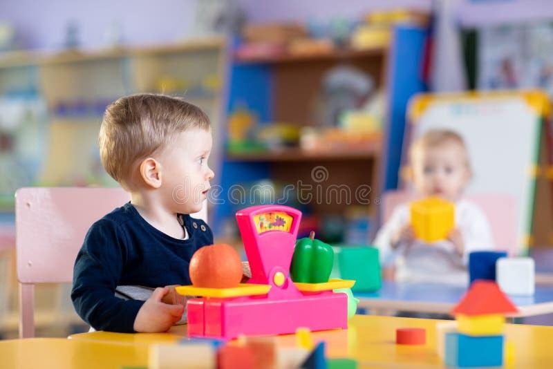 Weinig kindjongen zit bij lijst en speelt met stuk speelgoed schalen in speelkamer stock foto's