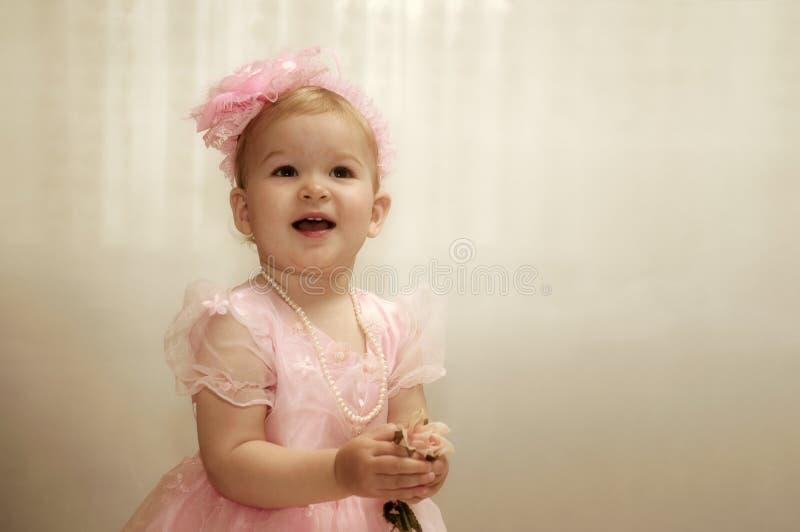 Weinig kindmeisje in elegante roze kleding met boog op hoofd op birt stock foto's