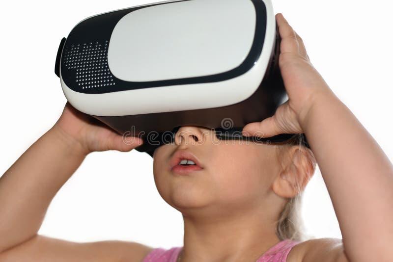 Weinig kindmeisje speelt een spel met virtuele werkelijkheidsglazen op witte achtergrond, vergrote werkelijkheid, helm, computers stock foto