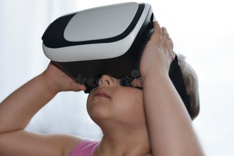 Weinig kindmeisje speelt een spel met virtuele werkelijkheidsglazen op witte achtergrond, vergrote werkelijkheid, helm, computers royalty-vrije stock fotografie