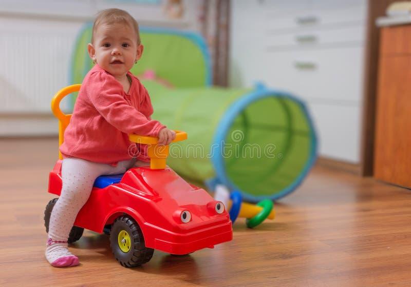 Weinig kindmeisje speelt, zit op rode stuk speelgoed auto en drijft het stock foto's