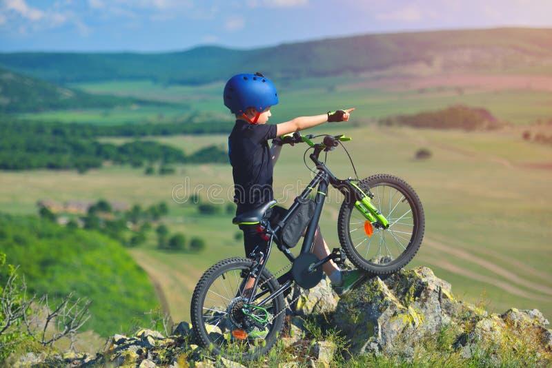 Weinig kindtribune naast zijn bergfiets op bergenrand en bekijkt het mooie landschap stock fotografie