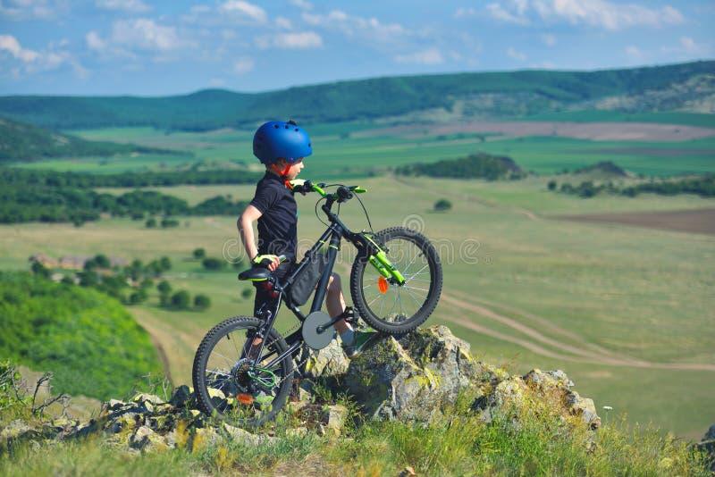 Weinig kindtribune naast zijn bergfiets op bergenrand en bekijkt het mooie landschap stock foto