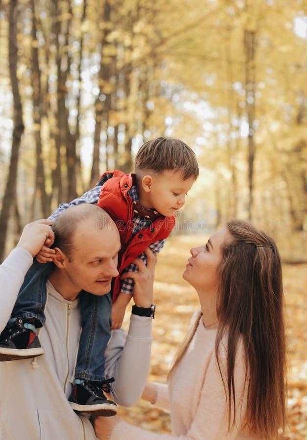 Weinig kindzitting op de schouders van de vader De moeder kust haar zoon stock foto