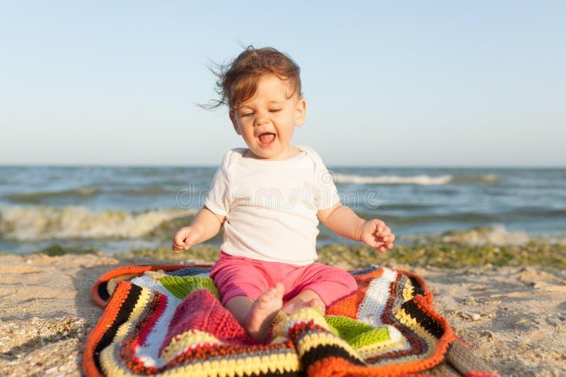 Weinig kindzitting op een gekleurde deken op de vrolijk en gelukkige kust royalty-vrije stock fotografie