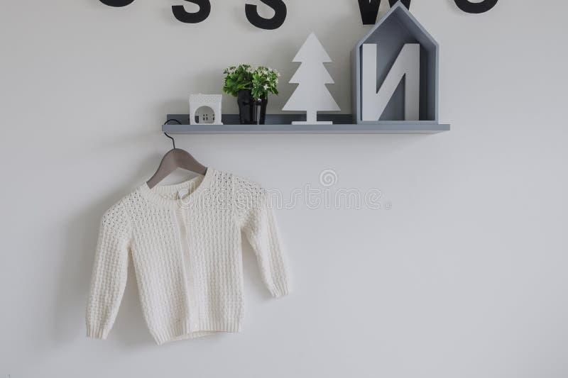 Weinig kleding voor kindmeisjes die op decoratieve plank hangen royalty-vrije stock afbeelding
