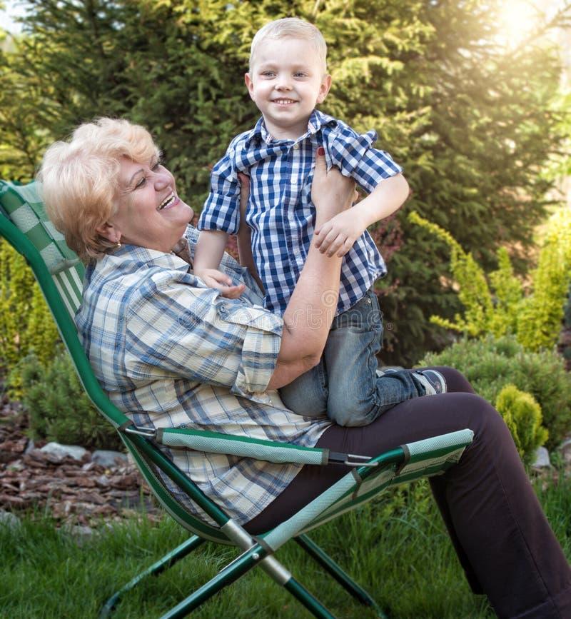 Weinig kleinzoon die grootmoederzitting in haar wapens koesteren Familievakantie in openlucht royalty-vrije stock afbeeldingen