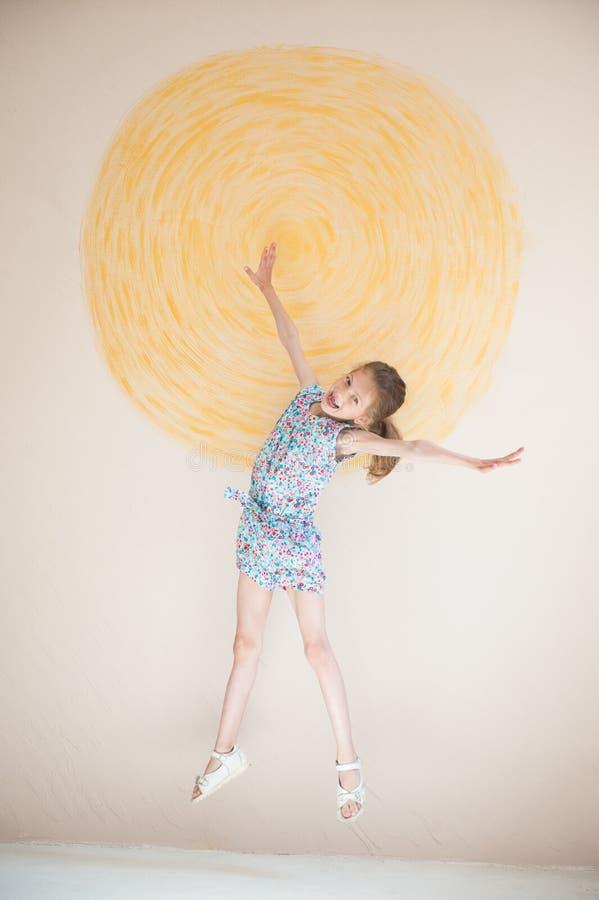 Weinig knap meisje die op muur met geschilderde gele zonachtergrond springen royalty-vrije stock afbeelding