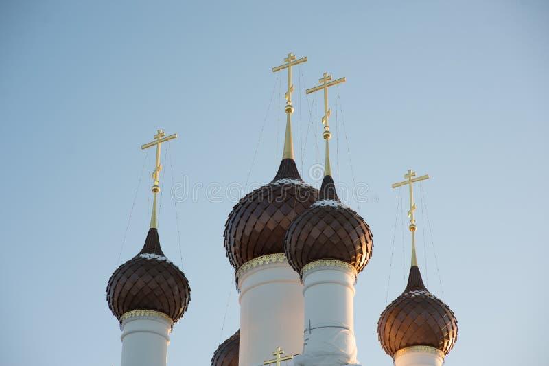 Weinig koepels met kruisen over een wit-stenen tempel tegen een blauwe hemel stock foto
