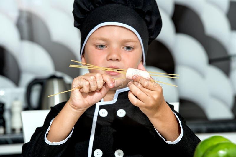 Weinig kok De jongen bereidt spaghetti in keuken voor stock foto