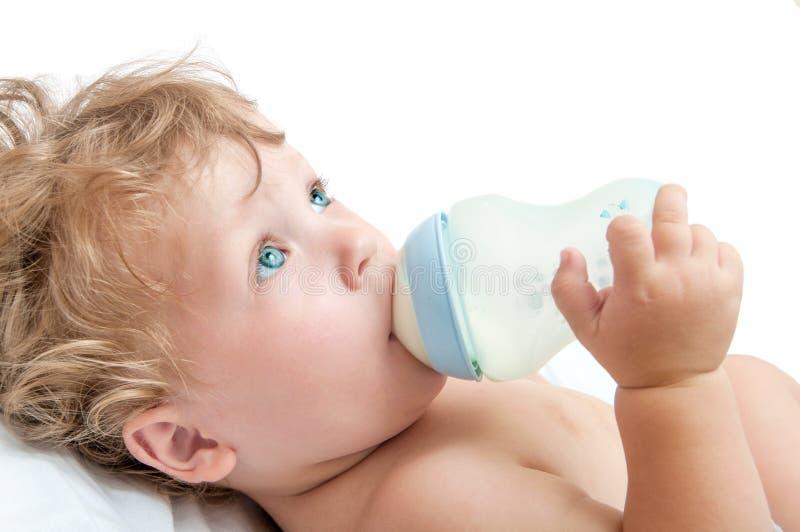 Weinig krullend-geleide baby zuigt een fles royalty-vrije stock fotografie