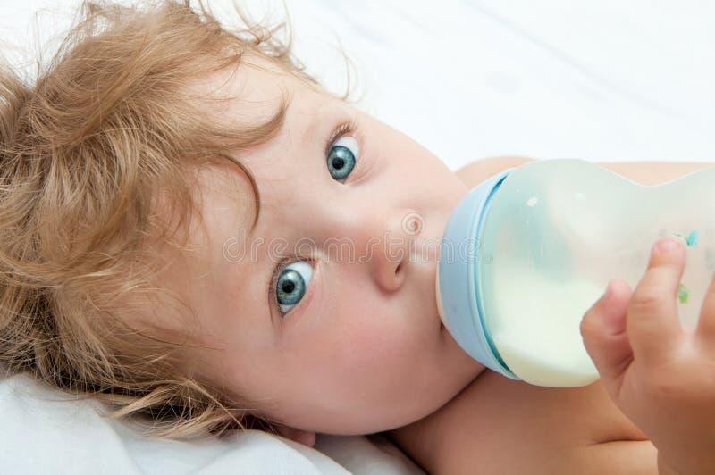 Weinig krullend-geleide baby zuigt een fles royalty-vrije stock afbeelding