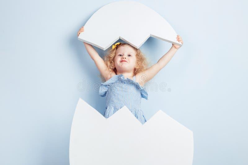 Weinig krullend meisje in de lichtblauwe kleding en gele bloem op haar haar schenen om van het grote witte ei uitgebroed te hebbe royalty-vrije stock afbeeldingen