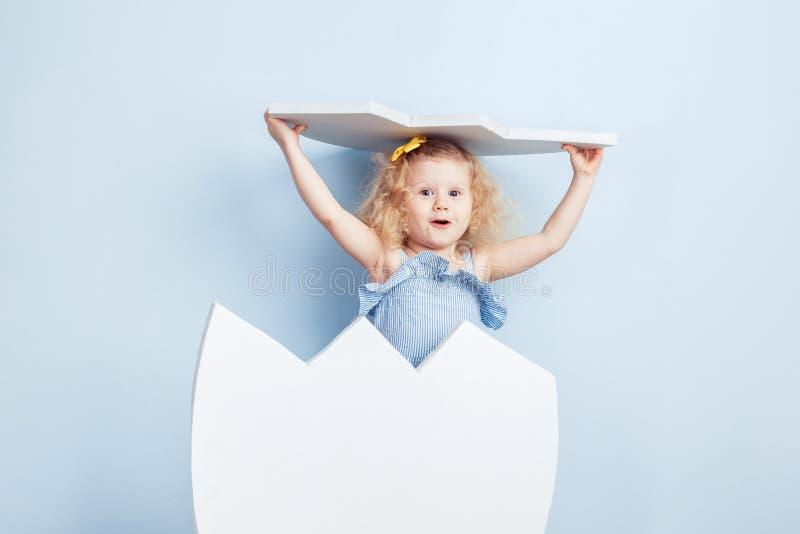 Weinig krullend meisje in de lichtblauwe kleding en gele bloem op haar haar schenen om van het grote witte ei uitgebroed te hebbe stock foto's