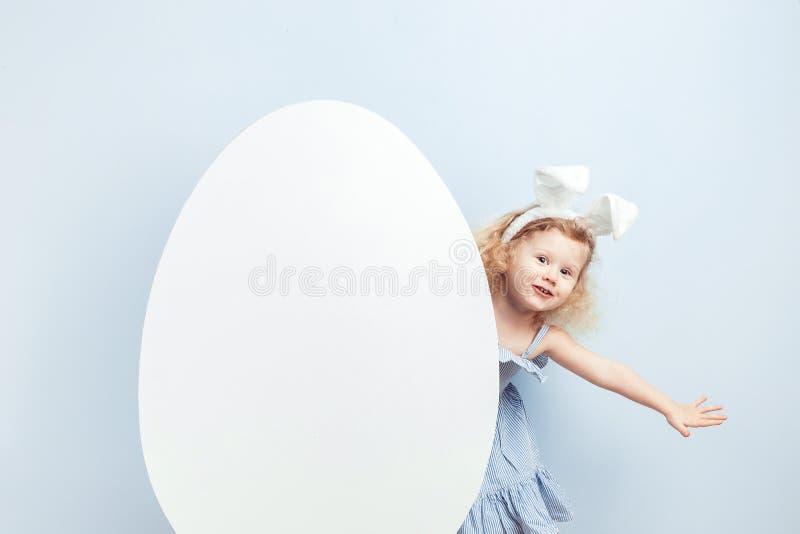 Weinig krullend meisje in de lichtblauwe kleding met konijntjesoren op haar hoofd kijkt uit van achter een groot wit ei tegen a stock foto's