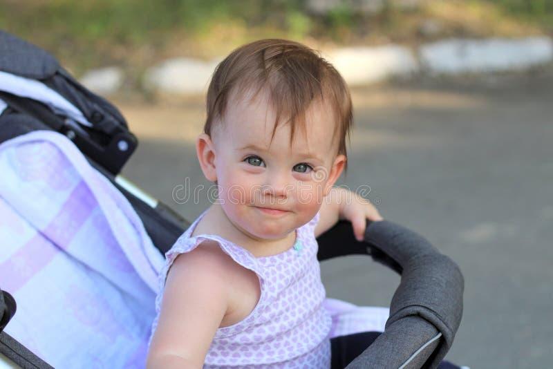 weinig, laat vallen de mooie, glimlachende, leuke roodharigebaby in een sleeveless overhemd in een kinderwagen uit-van-deuren ben stock fotografie