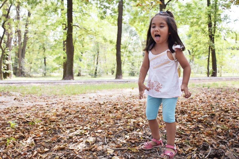 Weinig Latijns meisje die tong in het de herfstbos tonen stock afbeeldingen