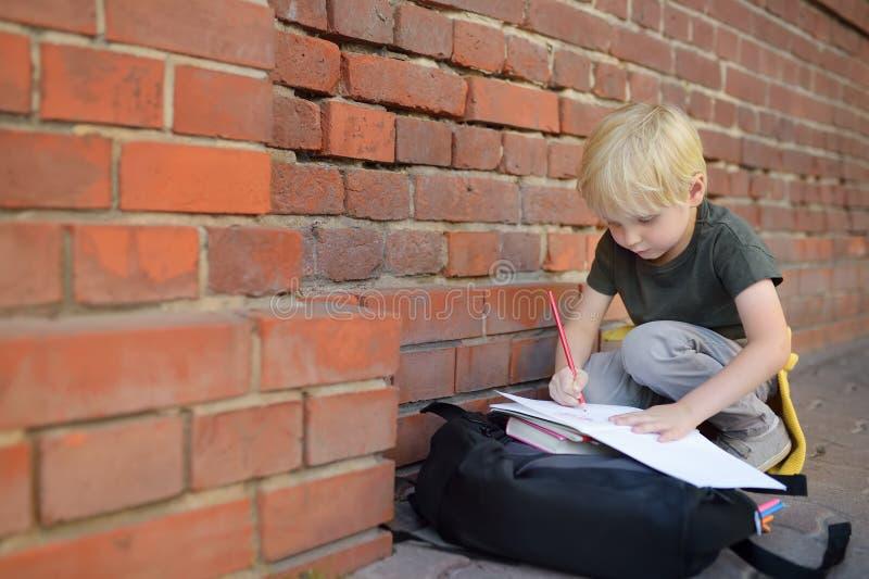 Weinig leerling die thuiswerk op onderbreking doet dichtbij de schoolbouw Terug naar het Concept van de School royalty-vrije stock afbeeldingen