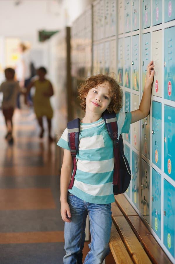 Weinig leerling die zich dichtbij kasten in schoolgang bevinden stock foto