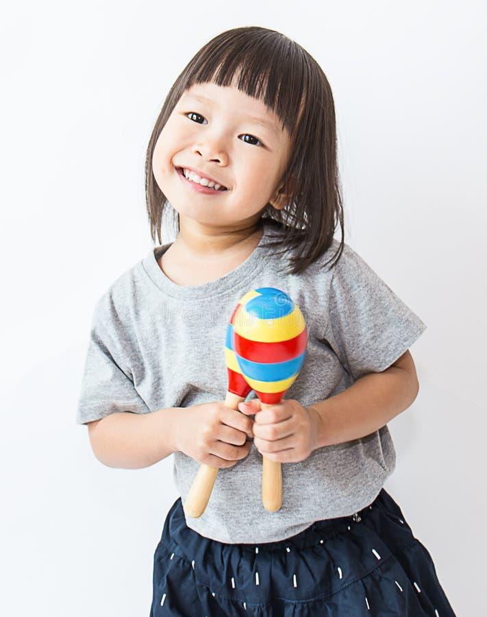 Weinig leuk Aziatisch meisje die maracas spelen royalty-vrije stock foto's