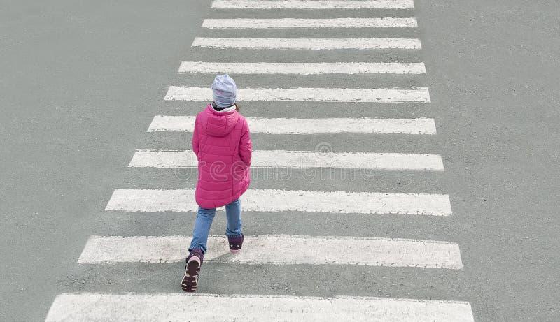Weinig leuk babymeisje gekleed in rood jasje, jeans, grijze hoed kruist de weg bij voetgangersoversteekplaats op koude dag Hoogst stock afbeelding