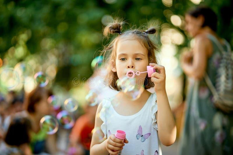 Weinig leuk babymeisje maakt zeepbels in het park op de zomerdag royalty-vrije stock foto's