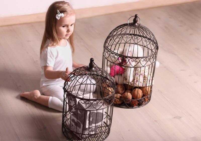 Weinig leuk blond meisje die in ruimte met kooien spelen die speelgoed vullen stock afbeeldingen