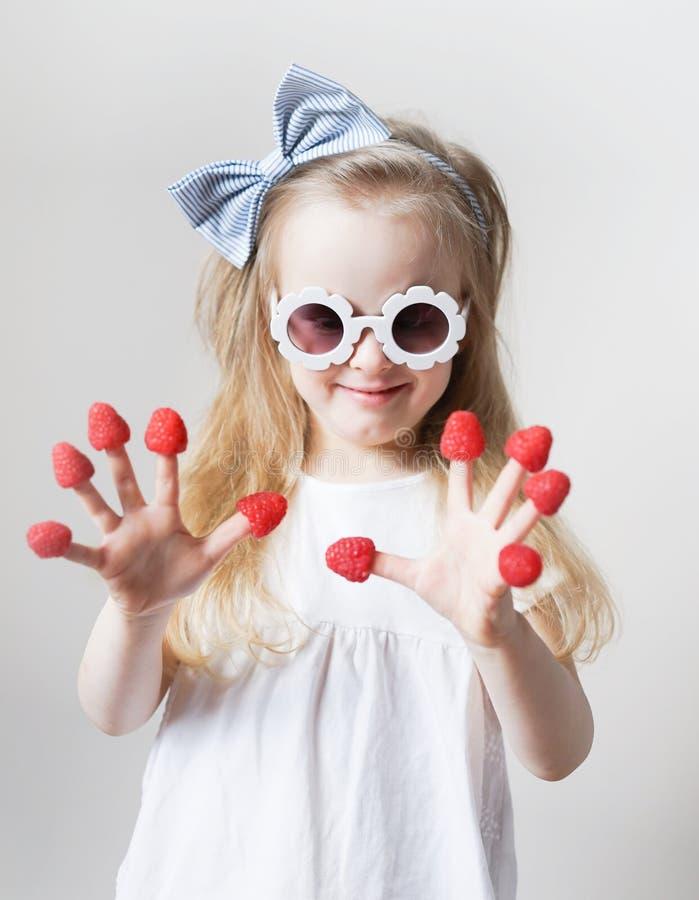 Weinig leuk blond meisje met frambozen in haar vingers, verschillende emoties, binnen stock foto
