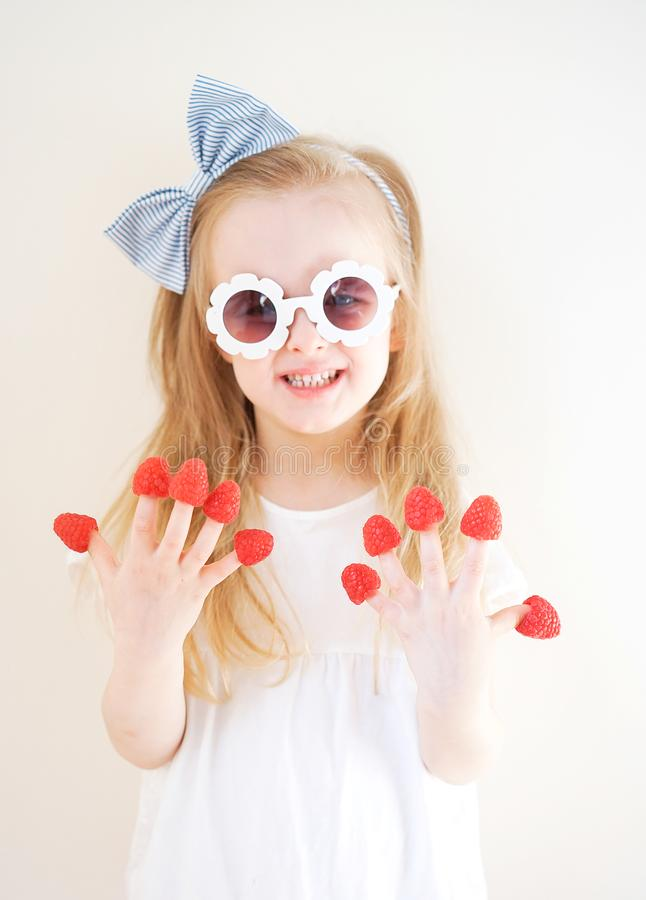 Weinig leuk blond meisje met frambozen in haar vingers, verschillende emoties, binnen royalty-vrije stock afbeelding