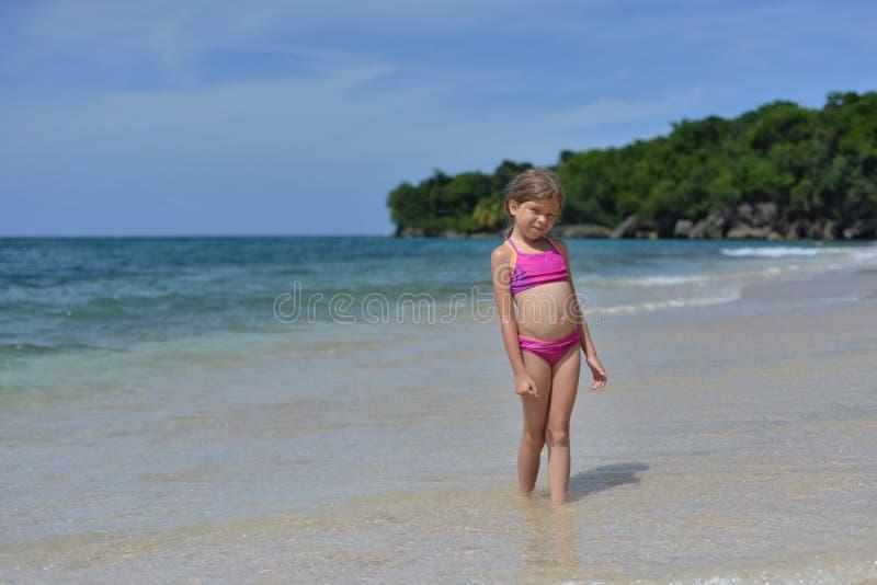 Weinig leuk blonde Kaukasisch meisje is op het tropische strand in de Caraïben royalty-vrije stock foto's