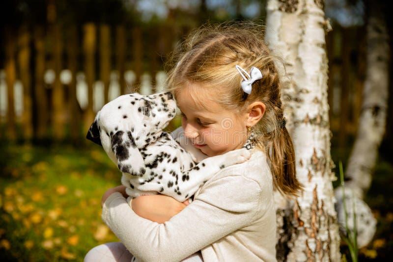 Weinig leuk blondemeisje die met haar Dalmatische puppyoutdoo spelen, op zonnige warme de herfstdag zorg van Huisdierenconcept Ki stock fotografie