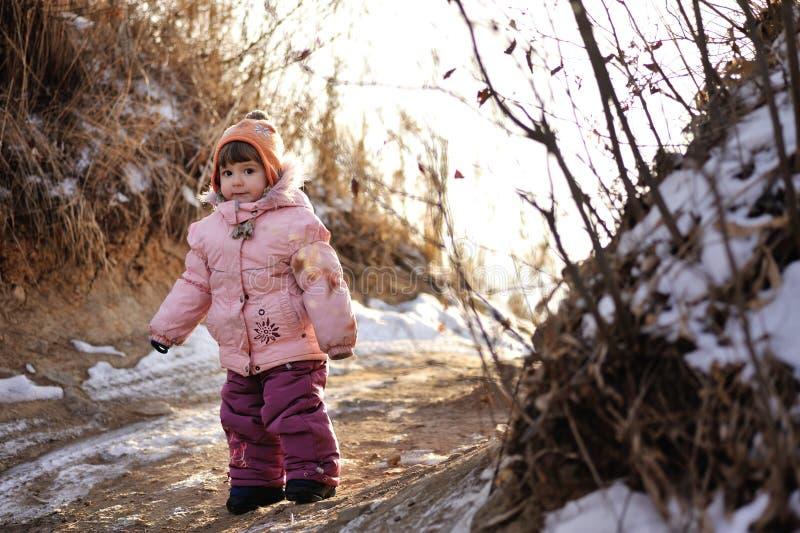 Weinig leuk en mooi meisje die zich op de weg en watchin Ti-camera bevinden stock fotografie