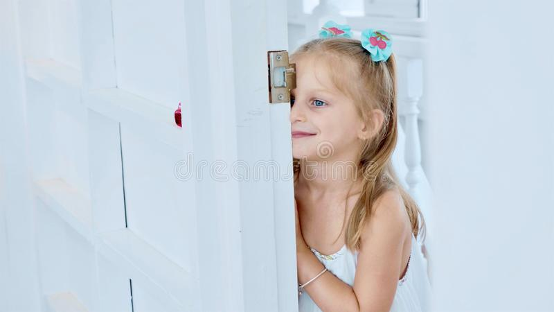 Weinig leuk kindmeisje gluurt door de deuropening in ruimte met grappige emoties stock foto's