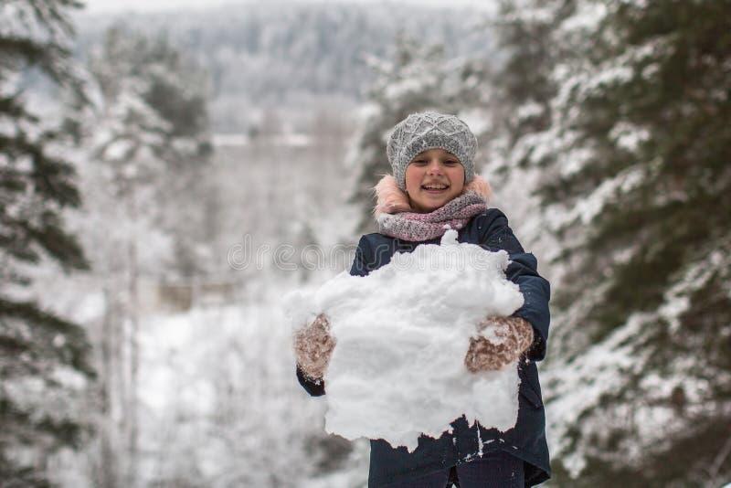 Weinig leuk meisje beeldhouwt sneeuwman spel stock afbeelding