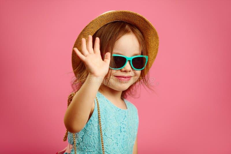 Weinig leuk meisje in de zomerhoed en zonnebril die bij u golven, uitdrukkend vreugde en geluk, die zich op geïsoleerd roze bevin royalty-vrije stock afbeeldingen