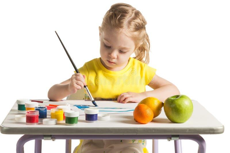 Weinig leuk meisje die aan het schilderen, op witte achtergrond leren stock foto