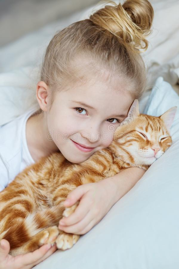Weinig leuk meisje die affectionately katje koesteren stock fotografie