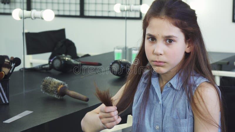 Weinig leuk meisje die droevig onderzoekend haar beschadigd haar met gespleten punten kijken royalty-vrije stock foto