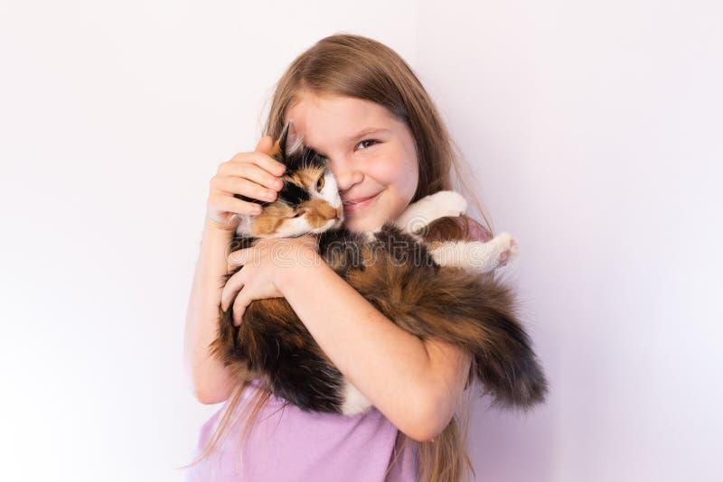 Weinig leuk meisje die een tricolorkat en omhelzingen houden haar, op een lichte achtergrond royalty-vrije stock foto's