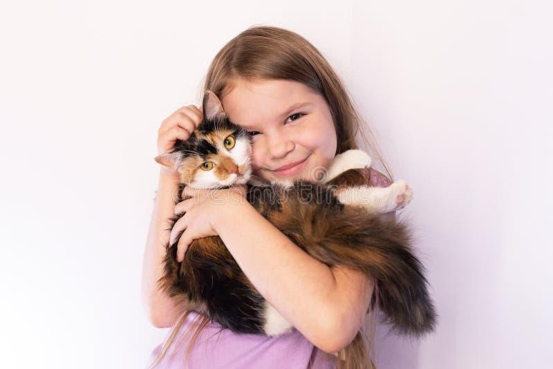 Weinig leuk meisje die een tricolorkat en omhelzingen houden haar, op een lichte achtergrond stock foto's