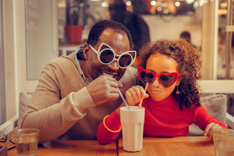 Weinig leuk meisje die haar milkshake met haar houdende van vader delen stock foto