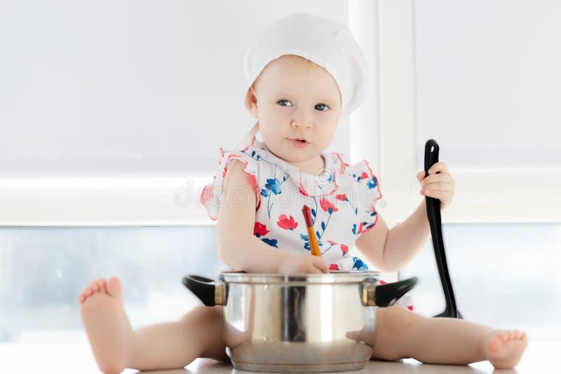 Weinig leuk meisje die in keuken met potten spelen stock afbeelding