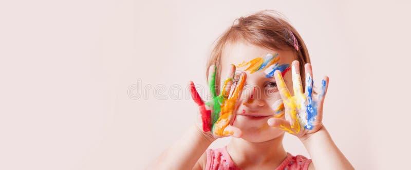 Weinig leuk meisje die met de kleurrijke make-up van kinderen geschilderde handen tonen Kinderjaren en kunstconcept stock foto