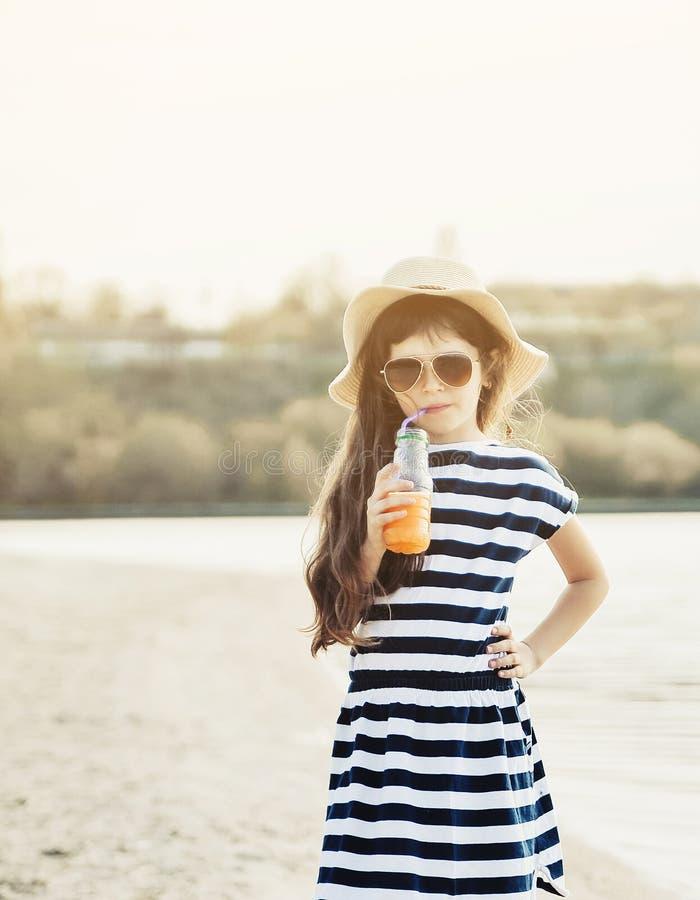 Weinig leuk meisje die op het het strand en het drinken jus d'orange lopen stock foto