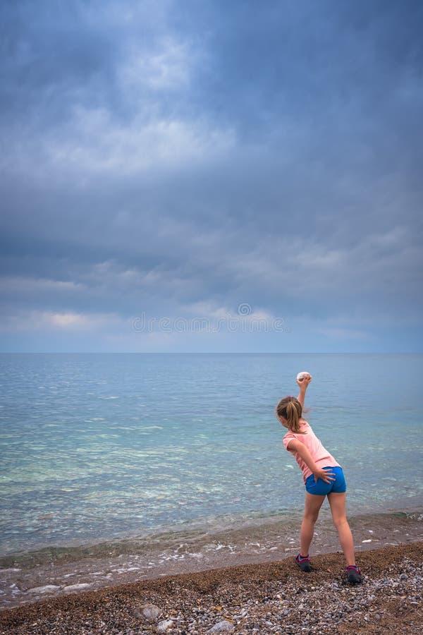 Weinig leuk meisje die steen werpen aan het overzees royalty-vrije stock foto